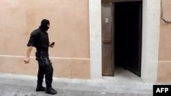 Seorang anggota pasukan khusus Perancis (GIPN) berjalan di depan sebuah rumah tempat diangkapnya dua orang yang diperkirakan anggota ETA di Montpellier, sebelah selatan Perancis (7/5).