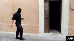 A member of the French police special forces (GIPN) walks in front of the house where two presumed members of ETA were arrested in Montpellier, southern France, May 7, 2013.