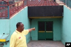 Congolese photographer Buddy Tshipamba points at the room from which boxer Muhammad Ali entered the stadium for his fight against George Foreman in Kinshasa, D.R.C., in October 1974.