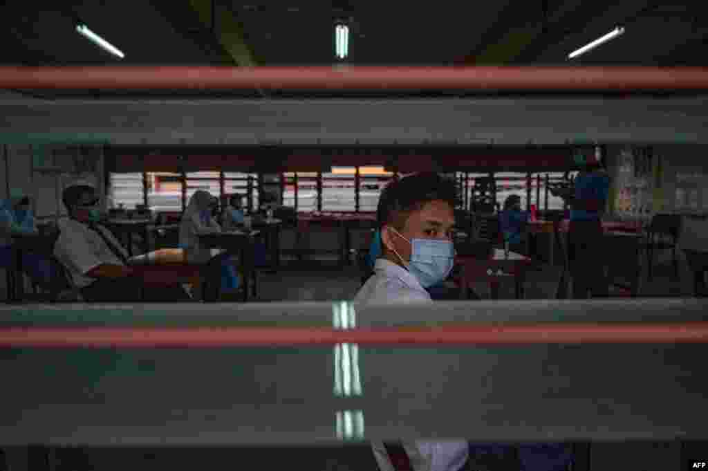 A high school student wears a face mask in a classroom on the first day after being reopened following restrictions to halt the spread of the COVID-19 coronavirus in Kuala Lumpur.