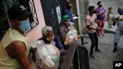 Residentes ayudan a descargar bolsas de alimentos básicos, como pasta, azúcar, harina y aceite de cocina, proporcionados por un programa de asistencia alimentaria del gobierno, en el barrio Santa Rosalía de Caracas, Venezuela, el sábado 10 de abril 2021.