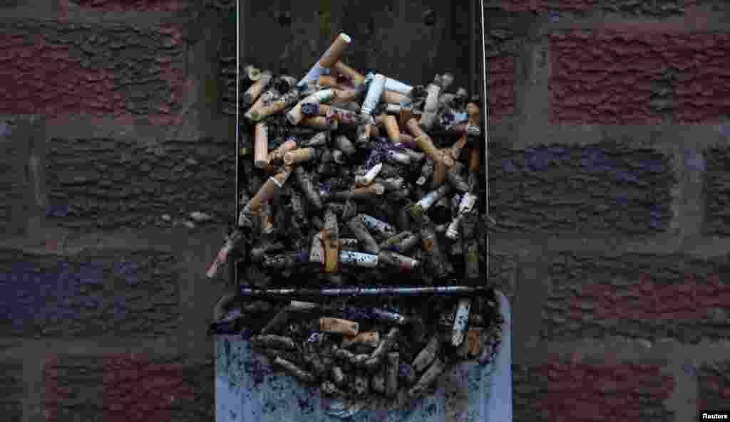 شمالی برطانیہ کے ایک شاپنگ سینٹر کی دیوار میں لگے ایک ایش ٹرے سے استعمال شدہ سگرٹوں کے ٹکرے باہر نکل رہے ہیں