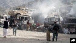 Cảnh sát Afghanistan canh gác gần các xe tải bị cháy sau vụ tấn công căn cứ Mỹ gần biên giới Pakistan, ngày 2/9/2013.