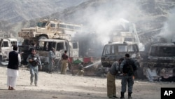 Afghan police stand guard near burning NATO supply trucks following an attack by militants on a U.S. base near the Pakistan-Afghanistan border, Sept. 2, 2013.