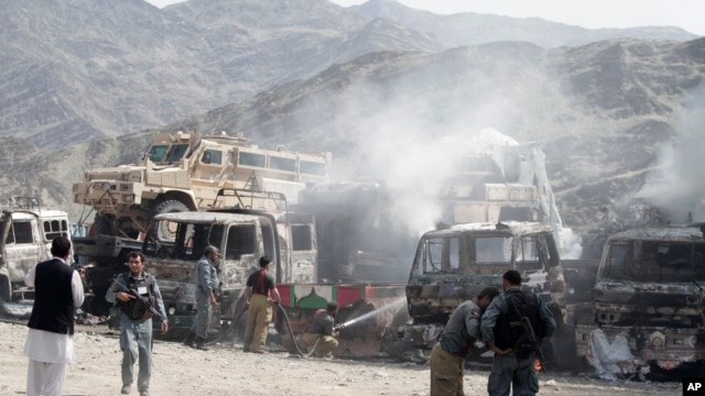 FILE - fghan police stand guard near burning NATO supply trucks following an attack by militants on a U.S. base near the Pakistan-Afghanistan border, Sept. 2, 2013.