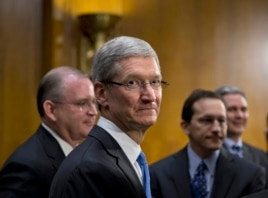 Apple CEO Tim Cook, center, is surrounded by his team during a break from testifying on Capitol Hill in Washington, May 21, 2013.