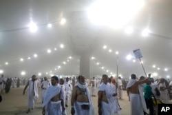 """Peziarah berjalan setelah mereka melemparkan batu ke pilar yang melambangkan rajam Setan, dalam ritual yang disebut """"Jamarat,"""" ritual terakhir haji tahunan, pada hari pertama Idul Adha, di Mina dekat kota suci Mekah Arab Saudi (Foto: AP / Mosa'ab Elshamy)"""