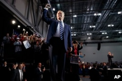 FILE - Republican presidential candidate Donald Trump pumps his fist as he arrives to speak at a campaign rally in Grand Rapids, Mich., Nov. 8, 2016. President-elect Donald Trump inherits a much sturdier economy than the one Barack Obama did.