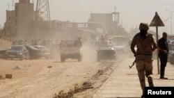 利比亚国民军成员进入一亲政府民兵组织的基地大门,之前示威者曾攻击该基地