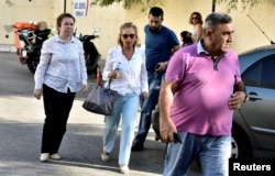 Turkish journalist Nazli Ilicak, center, a well-known commentator and former parliamentarian, is escorted by a police officer, right, and her relatives, at left and rear, after being detained and brought to a hospital for a medical check in Bodrum, Turkey, July 26, 2016.