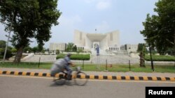 A man rides a bicycle past the Supreme Court building in Islamabad, Pakistan, June 27, 2016.