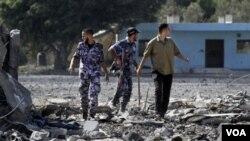 Pasukan keamanan Hamas memeriksa lokasi serangan udara Israel di kota Gaza, Minggu (21/8).