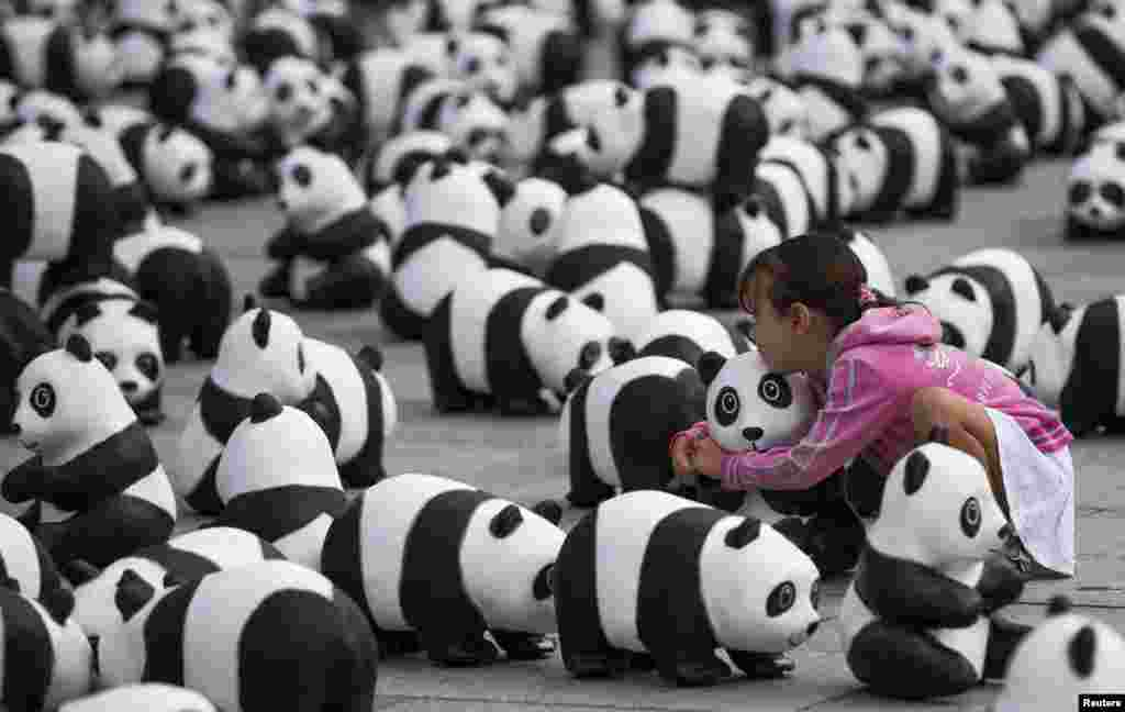 A girl embraces a panda bear sculpture in Berlin, Germany.