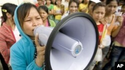 A Cambodian garment worker speaks on a loud speaker as she leads a strike in front of a factory on the outskirts of Phnom Penh, file photo.