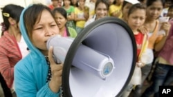 A Cambodian garment worker speaks on a loud speaker as she leads a strike in front of a factory on the outskirts of Phnom Penh, Cambodia, Monday, Sept. 13, 2010.