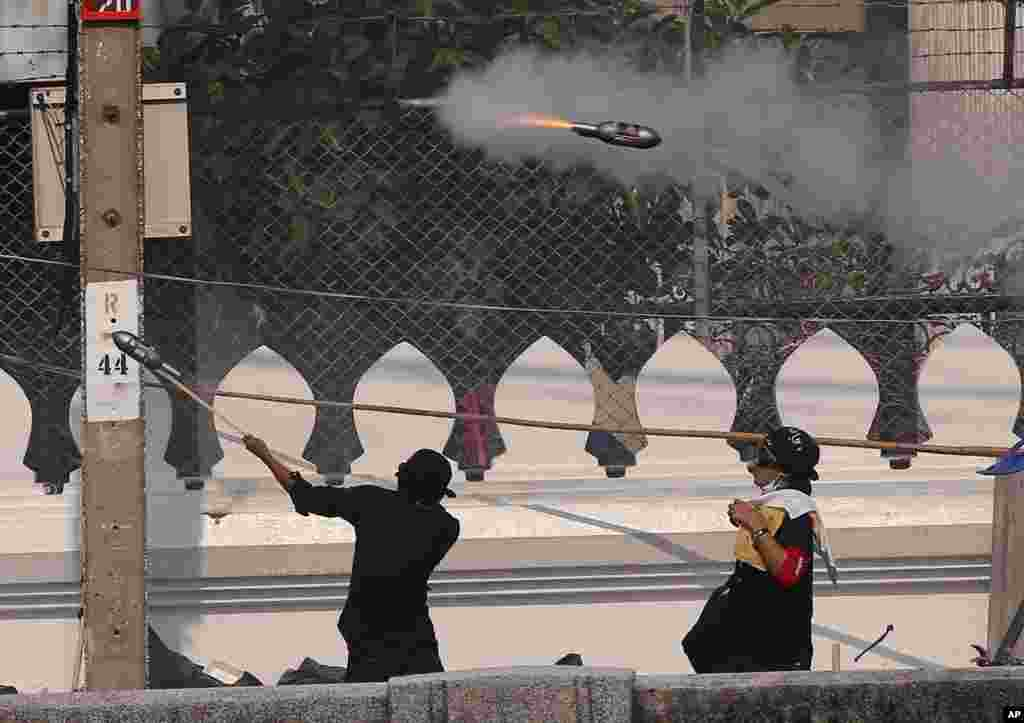 Anti-government protesters use a handmade rocket launcher to fire explosive material to riot police in Bangkok, Thailand.