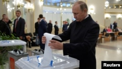 FILE - Russian President Vladimir Putin casts a ballot at a polling station during a parliamentary election in Moscow, Sept. 18, 2016.