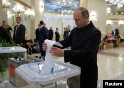 Russian President Vladimir Putin casts a ballot at a polling station during a parliamentary election in Moscow, Sept. 18, 2016.