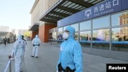 中國吉林省吉林市身穿防護服的警察站在停運的火車站進站口處。(2020年5月13日)