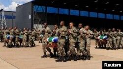 Des membres de l'armée sud-africaine portant la dépouille mortelle de 13 soldats qui ont été tués en République centrafricaine (RCA) lors d'une cérémonie à la base aérienne de Waterkloof, à Pretoria, 28 mars.2013