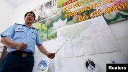 Đại tá Đỗ Đức Minh, Phó tham mưu trưởng Quân chủng Phòng không-Không quân Việt Nam cạnh bản đồ khu vực tìm kiếm chuyến bay MH370 bị mất tích trong một cuộc họp báo tại TPHCM, ngày 13/3/2014.