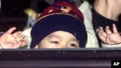 A North Korean asylum seeker's child waves to journalists from a bus after arrival at Incheon International airport in South Korea on 27 January 2003.