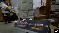 "FILE - A worker walks past a stack of books by former Beijing mayor Chen Xitong, titled ""Conversation with Chen Xitong,"" at a publisher's warehouse, one day before the launch of the book in Hong Kong."
