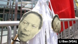 示威者用国旗下的白布条挂李旺阳头像抗议中共政权
