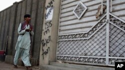 FILE - A man looks at graffiti supporting the Islamic State group as he walks past an entrance of a compound in Karachi, Pakistan, Nov. 12, 2014. Authorities in Pakistan are reported to have arrested five suspected IS operatives in Karachi Monday.