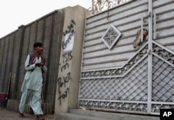 FILE - A man looks at graffiti supporting the Islamic State group as he walks past an entrance of a compound in Karachi, Pakistan, Nov. 12, 2014.