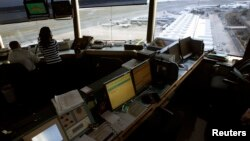 Reagan National Airport air traffic controller Sundie Yukich (2nd L) directs aircraft from the control tower in Washington, Feb. 28, 2013.