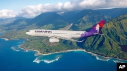 FILE - A Hawaiian Airlines plane flies above Hawaii.