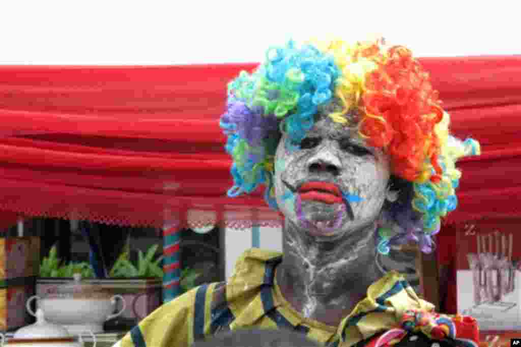 A Nigerian man dressed as a clown tries to attract customers to a market stall, in Lagos, Nigeria, Wednesday, Nov. 16, 2011. (AP Photo/Jon Gambrell)