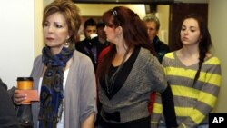 Family members and victims line up to get into court for a preliminary hearing for Aurora theater shooting suspect James Holmes at the courthouse in Centennial, Colorado, Monday, Jan. 7, 2013.