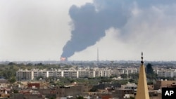 FILE - Black smoke billows over the skyline as a fire at the oil depot for the airport rages out of control after being struck in the crossfire of warring militias battling for control of the airfield, in Tripoli, Libya, July 28, 2014.