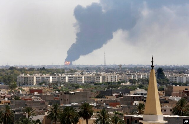 FILE - Black smoke billows over the skyline as a fire at the oil depot for the airport rages out of control, in Tripoli, July 28, 2014.