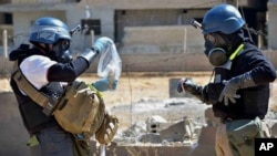 Members of a U.N. chemical weapons investigation team take samples, August, 2013. (FILE)