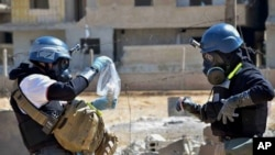 In this Aug. 28, 2013 citizen journalism file image, members of a chemical weapons investigation team take samples from sand near a part of a missile that is likely to be one of the chemical rockets, according to activists, in the Damascus countryside of Ain Terma, Syria. (AP Photo/United Media office of Arbeen, File)