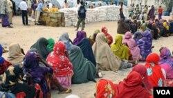 Mujeres somalíes aguardan para recibir alimentos en un campo de refugiados internos cerca de Mogadishu, la capital del país.