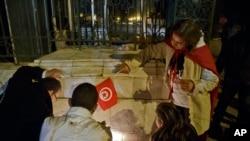 Warga Tunisia menyalakan lilin di pintu masuk Museum Nasional Bardo di Tunis, pasca serangan pria bersenjata 18 Maret 2015 (AP Photo/Michel Euler).