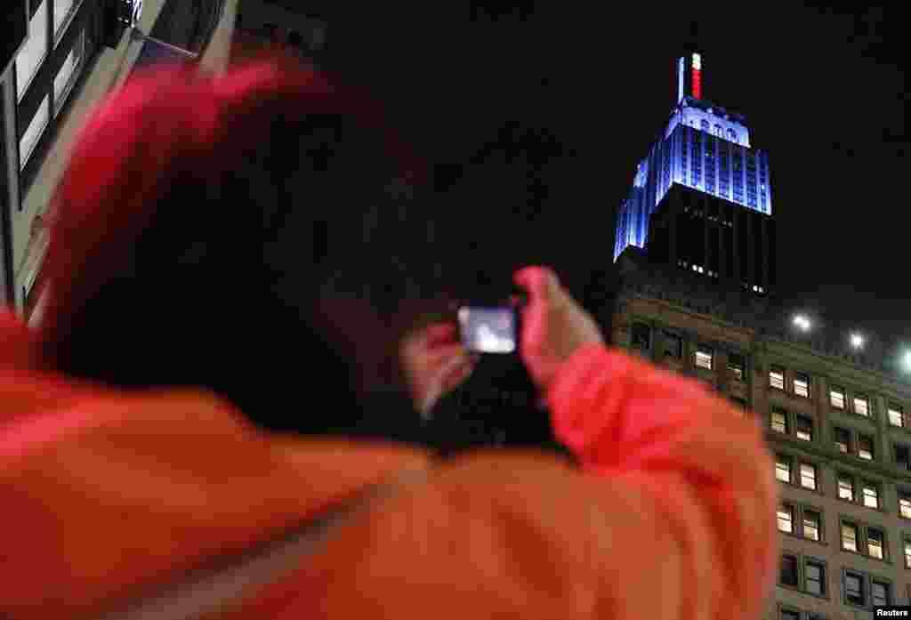 Une femme photographiant l'Empire State Building de New York, illuminé de la couleur bleue du Parti démocrate après la victoire de Barack Obama