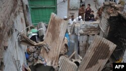 Pakistani residents look at a damaged house following an earthquake in Peshawar, on Oct. 26, 2015. AFP PHOTO / HASHAM AHMED
