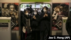 In this March 2, 2020, file photo, commuters wearing masks stand in a packed train at the Shinagawa Station in Tokyo. (AP Photo/Jae C. Hong, File)