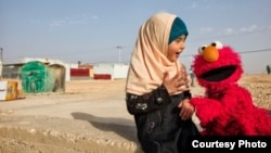 Elmo visits a young girl in a refugee camp. Sesame Workshop, together with the International Rescue Committee, have teamed up in an effort to provide quality education to young children displaced by conflict and persecution. (Photo courtesy of Sesame Workshop)