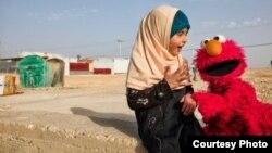 """Elmo mengunjungi seorang gadis kecil di sebuah kamp pengungsi. International Rescue Committee dan Sesame Workshop – LSM yang berada di balik program televisi """"Sesame Street"""" – memutuskan untuk membawa pendidikan langsung pada anak-anak pengungsi. (Foto: Sesame Workshop)."""