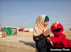 Elmo visits a young girl in a refugee camp. Sesame Workshop, together with the International Rescue Committee, have teamed up in an effort to provide quality education to young children displaced by conflict and persecution. (Photo: courtesy Sesame Workshop)