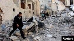 Warga memeriksa lokasi yang menjadi sasaran (yang oleh para aktivis disebut) serangan udara oleh pasukan yang setia kepada Presiden Suriah Bashar al-Assad di lingkungan al-Sukkari, Aleppo (4/2).