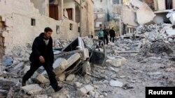 人们查看阿勒颇一处社区的废墟。活动人士说,当地遭到叙利亚政府军的空袭。(2014年2月4日)