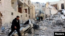 Men inspect a site hit by what activists said was an airstrike by forces loyal to Syria's President Bashar al-Assad in the al-Sukkari neighborhood in Aleppo, Feb. 4, 2014.