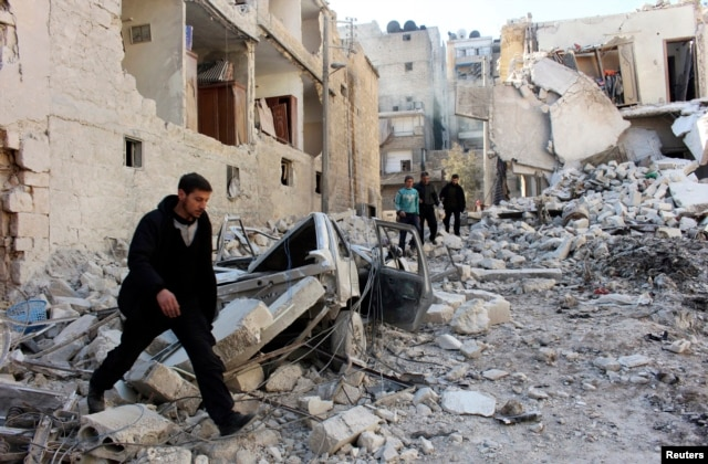 Men inspect a site hit by what activists said was an airstrike by forces loyal to President Bashar al-Assad in the al-Sukkari neighborhood in Aleppo, Feb. 4, 2014.